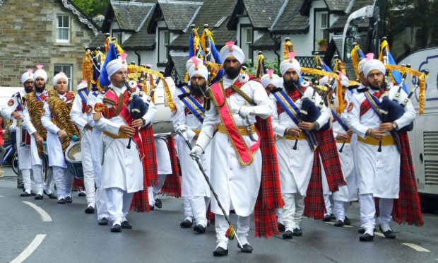 The Sikh Pipe Band march through Kenmore
