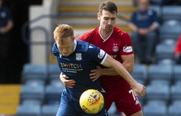 Dundee striker Danny Johnson battles with Aberdeen's Craig Bryson.