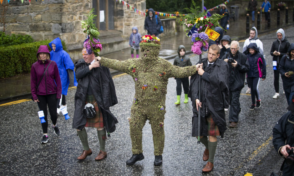 Burryman Andrew Taylor, accompanied by Andrew Findlater and Duncan Thompson , meets residents as he parades through the town of South Queensferry, near Edinburgh, encased in burrs. The parade takes place on the second Friday of August each year and although the exact meaning of this tradition has been lost through the years it is thought to have begun in the 17th Century. The tradition is believed to bring good luck to the towns people if they give him whisky offered through a straw or a donation of money.