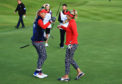Lexi Thompson (l) and Jessica Korda of Team USA celebrate after securing a half to restrict Europe's lead on the first day of the Solheim Cup.