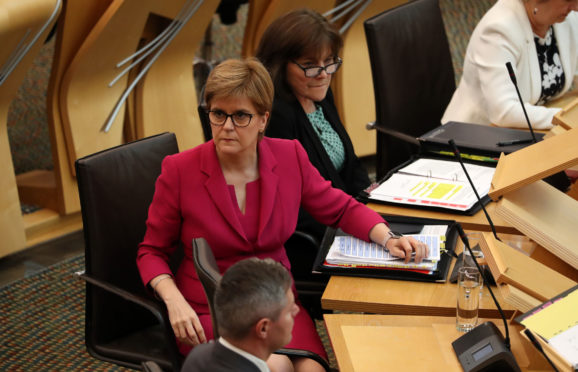 First Minister Nicola Sturgeon alongside Health Secretary Jeane Freeman in the debating chamber during First Minister's Questions at the Scottish Parliament in Edinburgh.