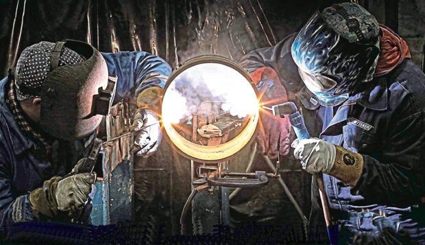 two welders welding a pipe in our workshop. Whittaker Engineering of Stonehaven