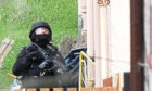 An armed police officer at the rear of a house in Kirktoun Street, Ballingry, Fife.