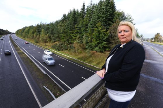 Councillor Lea McLelland with traffic on the A92 going under the bridge, near Cardenden today.