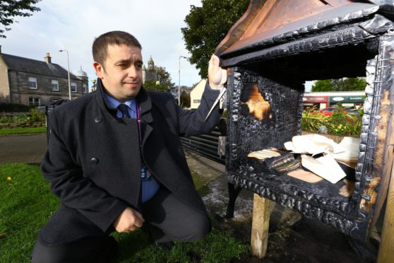 Local councillor David Graham surveys the damage done after the library was destroyed.