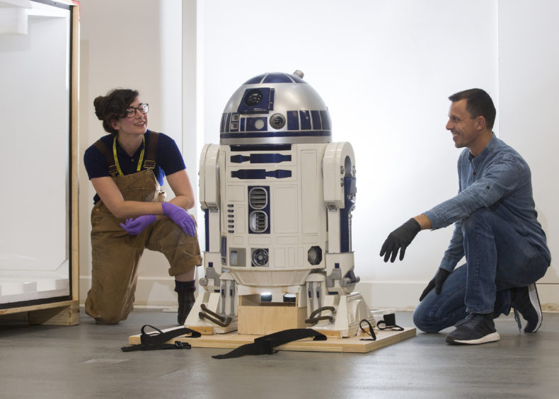 Patrick Luetzelschwab (VitraDesign Museum) and Jessie Staniland  (V&A Dundee) unboxing R2-D2.