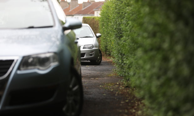Cars parked on pavements on Ancrum Drive, Dundee.