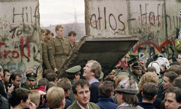 West Berliners crowd in front of the Berlin Wall early November 11 1989 as they watch East German border guards demolishing a section of the wall in order to open a new crossing point between East and West Berlin, near the Potsdamer Square.