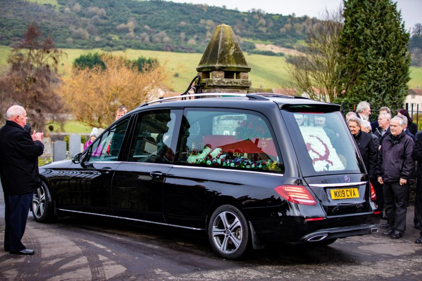 Funeral Director John Gilfillan leads the hearse to the cemetery.