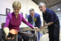 SNP leader Nicola Sturgeon, with SNP candidate for Ochil & South Perthshire, John Nicolson, and glass-maker Calum McDougall (right) makes a glass paperweight at Caithness Glass during a visit to Crieff Visitors Centre