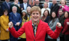 First Minister Nicola Sturgeon celebrates as she joins SNP's newly elected MPs for a group photo call outside the V&A Museum in Dundee.
