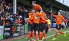 United number 12 Sam Stanton is mobbed after opening the scoring.