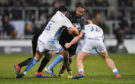 Leone Nakarawa is tackled by Sale Sharks's Rob Webber and Jake Cooper-Woolley at Sale.